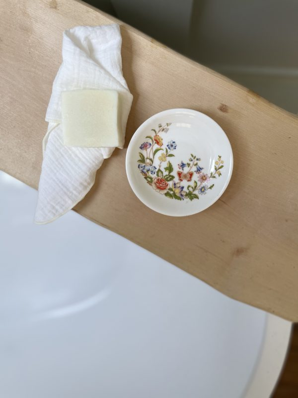 Vintage soap dish on a wooden table next to soap